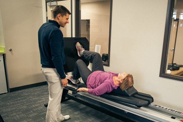 male physical therapist monitors female member performing one-legged leg press