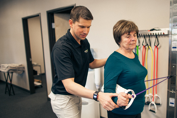 male physical therapist provides assistant to female client with exercise band