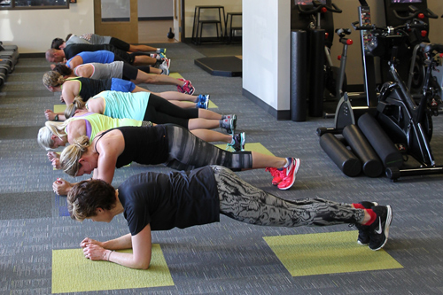 gym members perform plank pose