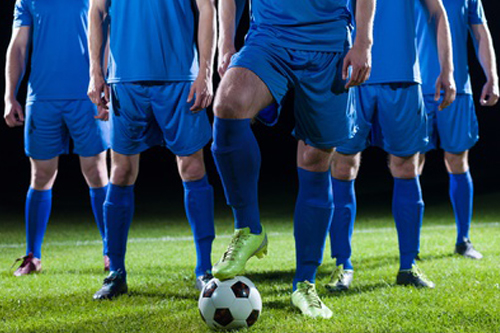 Soccer players on field, one player with foot on ball