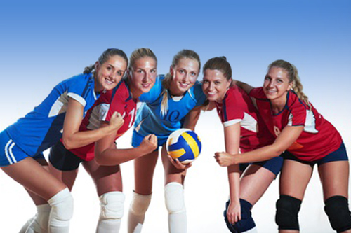 Young women holding volleyball