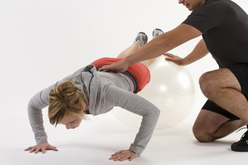 Personal trainer assists client doing a push up with feet on ball