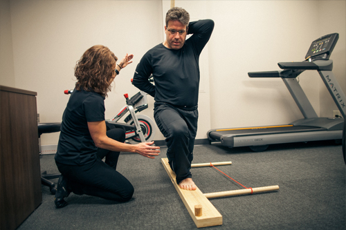 female physical therapist assists male perform lunge exercise