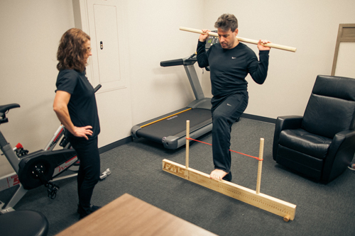 Physical Therapist monitors member's standing exercise