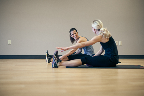 two female performing floor exercises