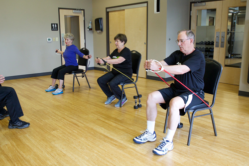 members of senior fit class perform seated shoulder raises