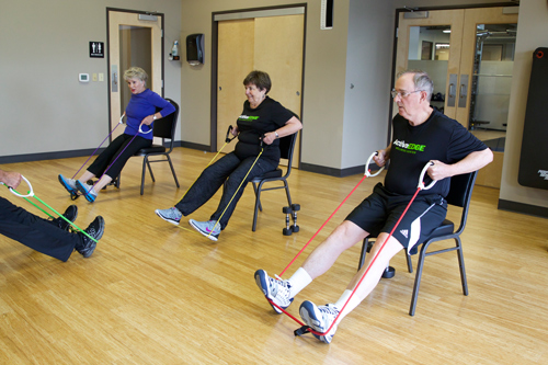 members of senior fit class perform seated rows with exercise bands