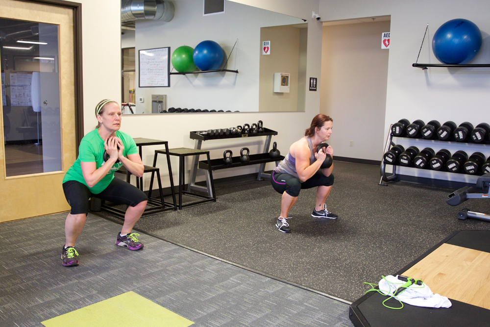 two females performing squat exercise with kettleball