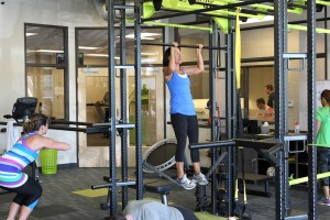 female doing pull-up on bar in health club