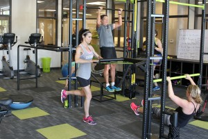 people performing exercise in gym room