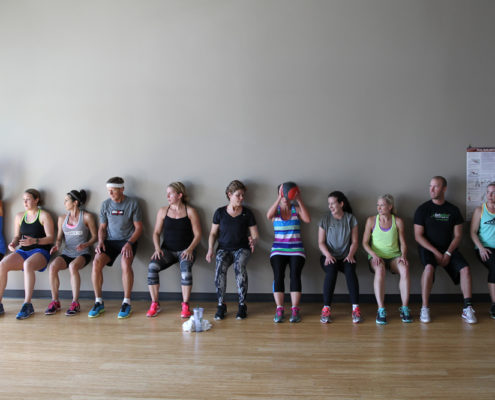 people along wall perform wall squat exercise