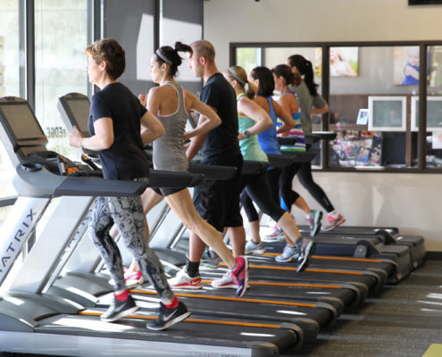 people exercising on treadmill machines