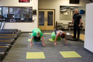 male personal trainer monitors two female clients performing floor exercises with exercise ball