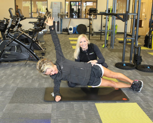 Physical therapist instructs client with floor exercise